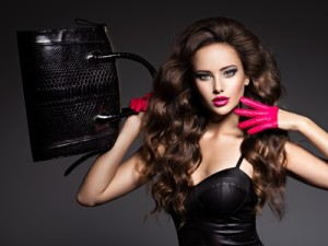 Beautiful woman with long hair in red gloves holds black handbag